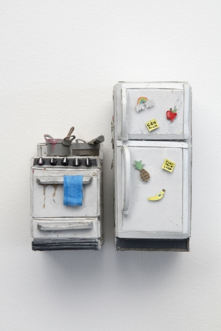 A stove with two dirty pots upon it and a closed refrigerator, crafted from paper and foam. The two items are next to each other with a small space between them, hung on the wall. The fridge has magnets on the exterior, and the stove has a towel hanging on the handle.