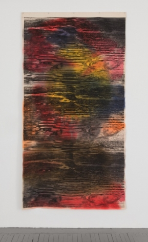 A photograph of the mixed media artwork hanging on the wall like a tapestry. There are abstract black lines upon it that ebb and flow like static on a television. The predominantly colors otherwise in the artwork are pink, red, yellow, navy, and white.