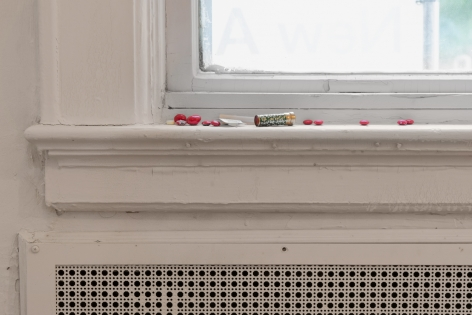 A close up photograph of the window sill with lipstick, red M&Ms, and illegible packs of over-the-counter drugs