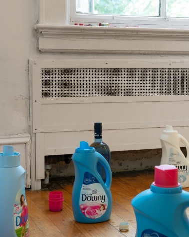 A photograph close-up of open detergent bottles and lipstick, M&Ms on the windowsill