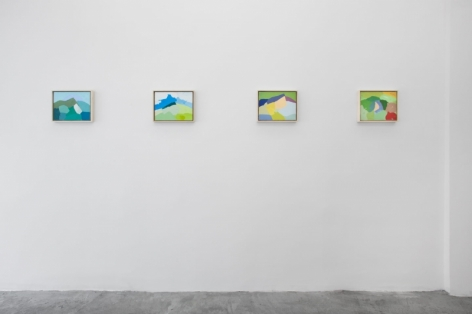A photograph of 4 technicolor abstract landscapes hung on the wall