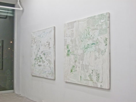 A photograph of 2 square abstract paintings on the wall