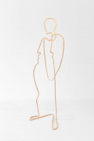 A plywood sculpture that is meant to look like a single carved line. The line describes a silhouette of a figure, seemingly leaning backward with elbows bent.