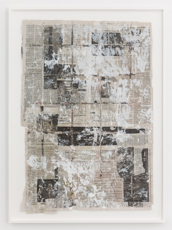 A painting on pages of newspaper, framed in white. The paint is mostly white.