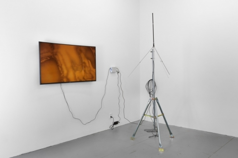 A photograph of the publicly visible portion of the artwork: a flat videoscreen at left installed on the wall. At right is a transmitter set upon the wall, and the antennae stands in the middle of the room on a tripod.