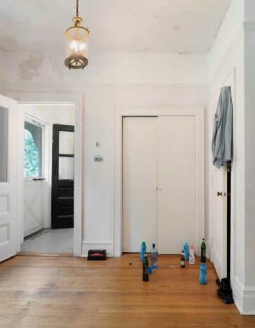 A photograph of the installation with a shirt on the door at right, and bottles of detergent and liquor on the ground