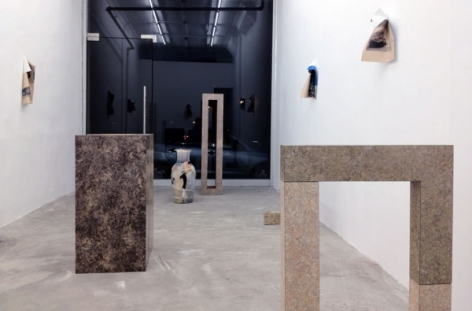 A photograph looking toward the front of the gallery: there are 5 sculptures on the floor and 3 photoworks on 2 walls