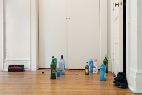 A photograph of bottles of detergent and liquor on the ground with a rat trap at left