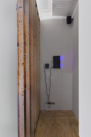 A photograph of the view behind the wall of the speaker projecting the sound into the gallery over a temporary wall.