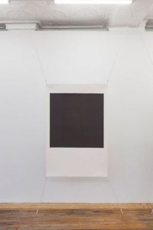 A photograph of one screenprint, stretched at all 4 corners. The center is black and the framed around it is white. The work resembles a polaroid in it's arrangement.
