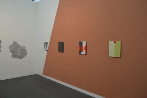 A photograph of the back wall of the installation, with 4 Ulrike works and 1 AK Burns metal shirt
