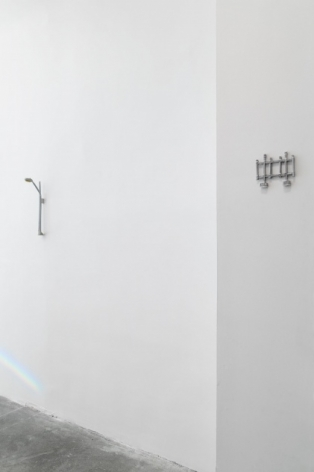 A photograph of the gallery wall: there is a paper streetlamp at left, and a small grey fence on the mini wall at right.