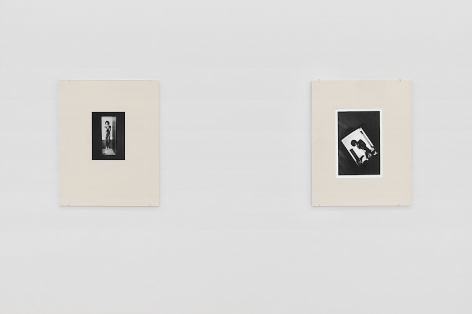 An installation view of 2 black and white Guibert photographs, placed in cream-colored frames made from watercolor paper, hung on the wall