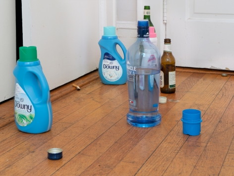 A photograph of detergent and liquor bottles on the ground with a smoked cigarette