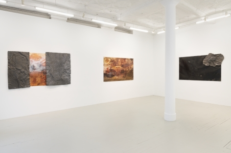 three paintings hanging on the wall where both works have orange brown and white colors in gestures that look like tumultuous sea scapes and the painting on the left has textured metal components attached to the surface, and the third painiting is solid black with a small metal sculpture attached to the upper right corner