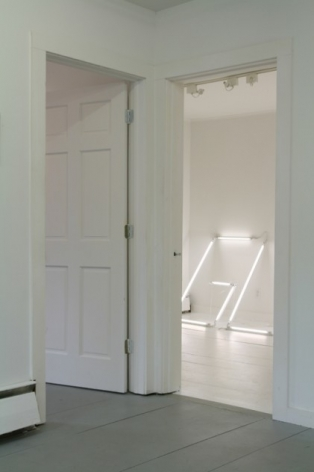 A photograph of 2 open doorways. At the right are the letters G-L in white neon