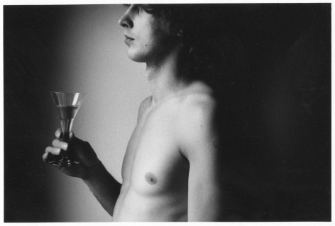 A black and white photograph of Eugene in side profile, from his elbow upward to his forehead. His shirt is off and we see his naked chest. At left he is holding a glass half-filled with liquid. The source of light comes from the left; the area behind him in the photograph is black.