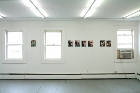 A photograph of 7 images across a white wall, with 3 windows among them