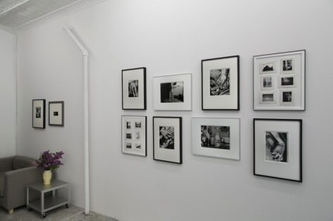 A photograph of 10 image, framed, hung salon style in the gallery.