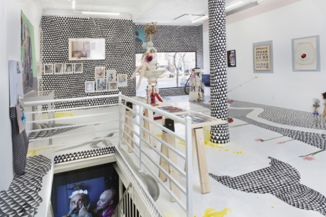 A photograph of the gallery from the back corner looking toward the door. A view of the basement staircase, showing a video at the bottom, is at left. The rest of the room is filled with flat works installed on the wall, mixed media sculptures installed on the ground, and a site-specific installation of black and white triangles on the ground and walls.