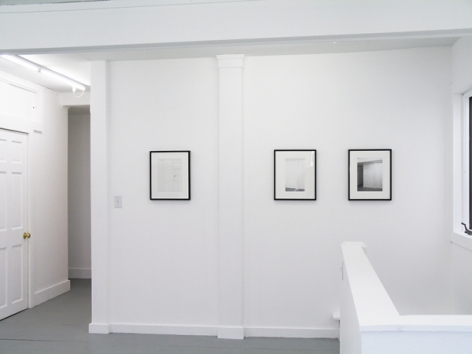 A photograph of 3 works framed in black on a white wall