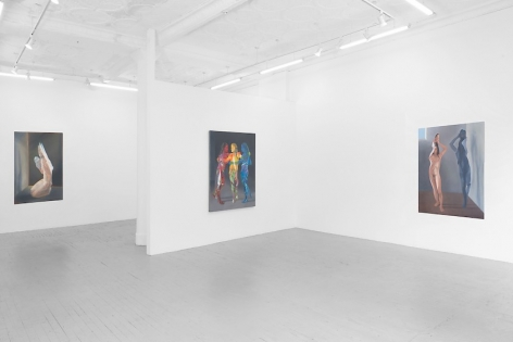 A photograph of the three large paintings: one of a single female figure not unlike a paper doll, folding over herself, at right; a painting of three figures in red, yellow, and blue on the temporary wall; and a painting of a naked female figure kneeling, looking like she's made of cellophane.