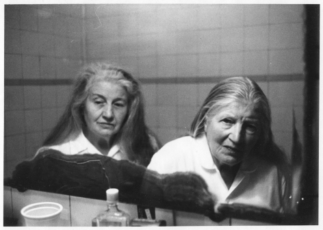 A black and white photograph of 2 elderly women, taken in a bathroom mirror. There are white tiles in the background, and tops of bottles and cups in the foreground.