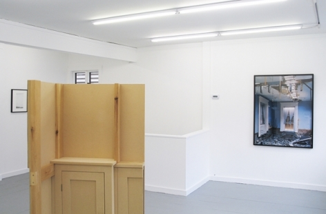 A photograph of the back of the sculpture in the center of the gallery, with one work at a wall at left and another at right on the wall