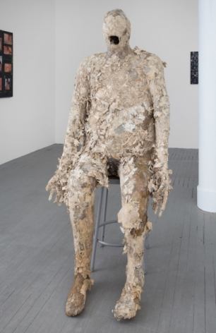 A figurative sculpture sitting on a stool that appears to be made of layered paper. The sculpture could be dissolving or decomposing. There are no facial features other than an open mouth, and there is a hole near the genitals.