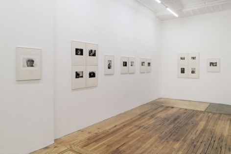 A wider photograph of the front quadrant in the gallery with 18 images, all of which are installed with cream mattes and silver frames.