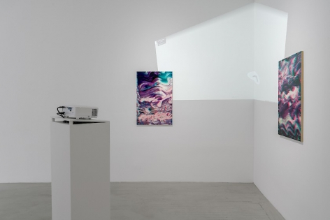 Two artworks are seen facing each other around the corner of the gallery. In the foreground is a projector on a white pedestal. On the wall on the corner is a white light, which is a video from Google Maps projecting the interior of the gallery onto itself.