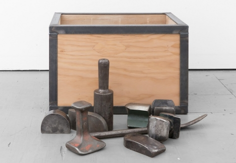 A photograph of the sculpture with it's contents brought out. The dollies made of steel are embossed and rusted.