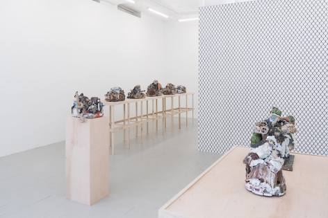 A photograph that partially captures the square raw wood table, and we see 2 ceramic sculptures, blurring together somewhat. There is a single raw wood pedestal in the middle ground, and a long table at left, along the wall. On the long table are 5 sculptures. At right in the middle ground we see the chainlink fence wallpaper on the gallery's temporary wall.