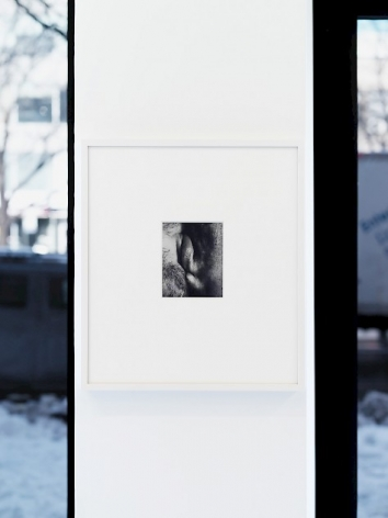 A photograph framed in white on a skinny white wall. The small black and white photograph, 1/4 the size of the frame, seems like two lips smacking against one another.