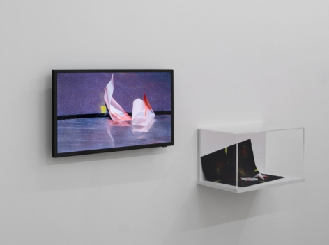 A photograph of the artwork in the exhibition that illustrates the video on a flat-screen TV, with the paper itself in a small vitrine at right upon the wall.