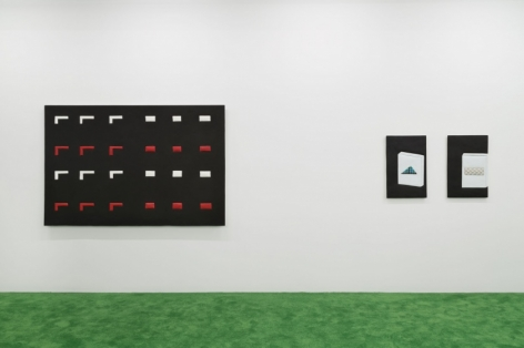 A photograph of one large black, white, and red artwork on the left, and 2 smaller flat artworks that depict a cigarette carton on each surface, abstracted.