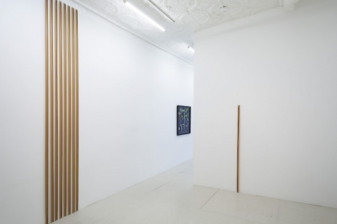 An installation view of 2 gummed paper tape installations by Thomas Kovachevich, one is 8 vertical strips installed floor-to-ceiling, and the other is the artist's height (5'9)