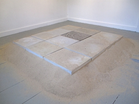 A site specific installation of 12 tiles on a bed of sand