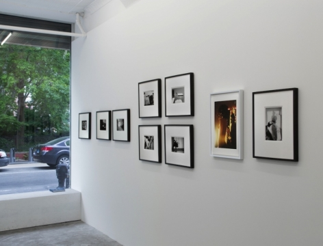 A photograph of 9 images on a white wall. At left is the window of the gallery looking outside