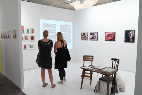 A view of the booth with 2 women inside, looking at art