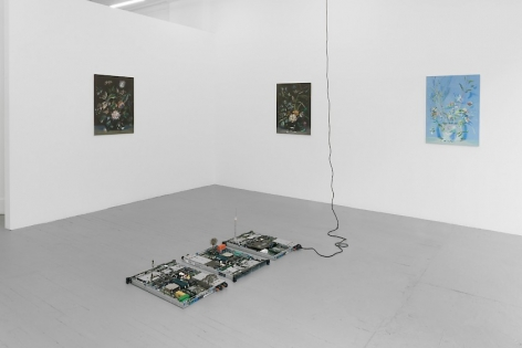 A photograph of the gallery with 3 paintings on the front wall, and a circuit board sculpture on the ground. The 2 paintings at left are black with color. The painting at right is in tones of blue and green.