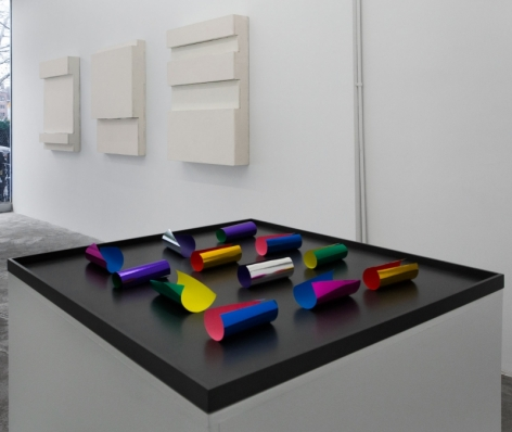 A photograph of a sculpture on a pedestal, with 3 works on a wall in the background
