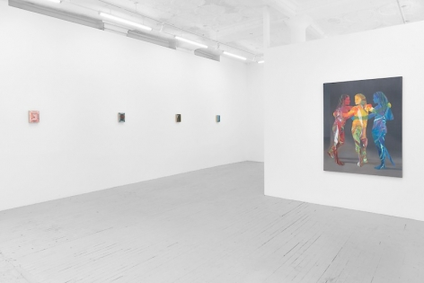 An angled photograph of the temporary wall, and four small paintings on the wall at left who's paintings are indiscernible.