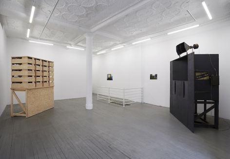 A photograph of the gallery that depicts two large structures in the room (at left, made of natural wood; at right, a black structure with a speaker on top). On the back wall at right, there are 2 illegible photographs.