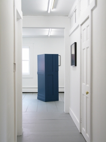 A photograph of a sculpture installed on the floor that resembles panels of a wall painted navy blue. There is a work on the wall at right that is illegible