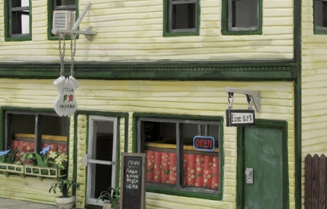 A photograph of the facade of the building that housed Callicoon Fine Arts in Callicoon, NY, made from foam core and paper. This is a close-up: it is a yellow building with green trim and doors. There is an Italian restaurant on the first floor.