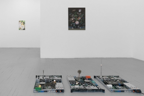 A frontal view of the gallery, with the circuit board sculpture in the foreground. Just behind it we see a still life painting on black ground, and in the distance is an abstract, multi-colored painting.
