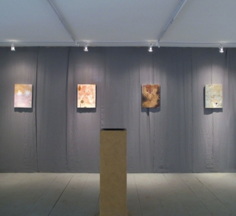 A photograph of 4 works on a gray wall, and a wooden pedestal in the middle