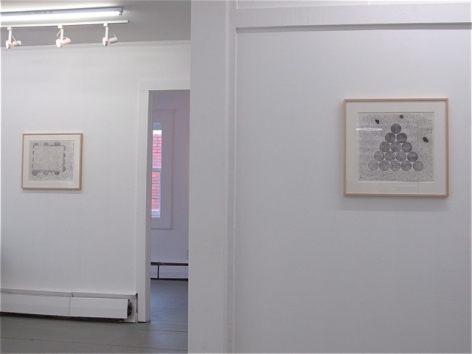 A photograph of 2 framed abstract works, one at right and another at left in the background