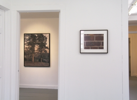 An image from outdoor the small room with a large photograph, and a smaller one outside the door